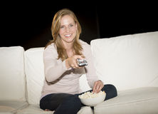 Woman Watching TV While Having Popcorn On Sofa Stock Photography