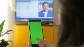 A woman is watching TV, and is holding a smartphone with a green screen. On the TV show the news.