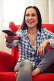 Woman watching tv at home. Excited woman watching tv at home Royalty Free Stock Photography