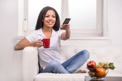 Woman watching tv at home and holding a remote control. Royalty Free Stock Photo