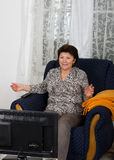 Woman watching TV. Older woman watching her favorite TV show Stock Images