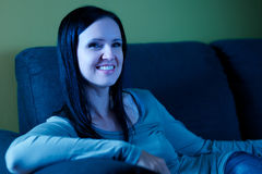 Woman watching TV. Pretty woman watching TV sitting on couch Royalty Free Stock Image