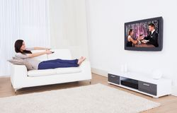 Woman watching tv while relaxing on sofa Stock Images