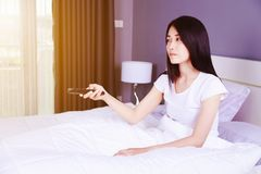 Woman watching tv with remote on bed in bedroom. Woman watching tv with remote on bed in the bedroom Royalty Free Stock Photos