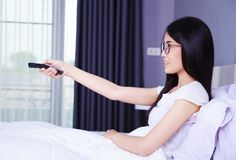 Woman watching tv with remote on bed in bedroom. Woman watching tv with remote on bed in the bedroom Stock Photo