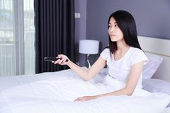Woman watching tv with remote on bed in bedroom Royalty Free Stock Photography