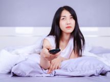 Woman watching tv with remote on bed in bedroom. Woman watching tv with remote on bed in the bedroom Stock Photos
