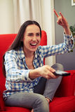 Woman watching tv and showing rock sign Stock Photos