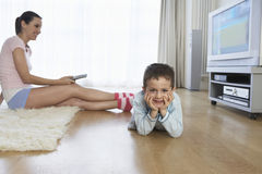 Woman Watching TV By Son On Floor Royalty Free Stock Photos
