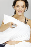 Woman watching TV. Young woman watching TV in bed with a remote control Royalty Free Stock Images
