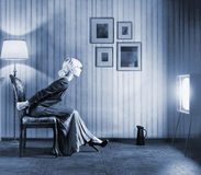 Woman  watching  tv. Young  woman sitting on a chair in vintage interior  and watching retro tv. She is very astonished while watching tv in dark room Stock Photography