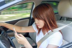 Woman watching video or text to someone with smart phone while d. Riving fast a car distracted Stock Photography