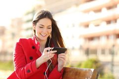 Woman watching videos in a smart phone with earphones. Sitting in a park with an unfocused buildings in the background Stock Images