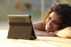 Woman watching videos on a tablet at sunset. Close up of a woman watching videos on a tablet in the evening at sunset in a park table Royalty Free Stock Image