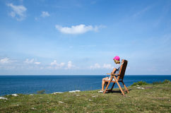 Woman watching view at coastline from a chair Royalty Free Stock Images