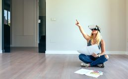 Woman watching with virtual reality glasses. Young woman watching the decoration of her house with virtual reality glasses royalty free stock photo