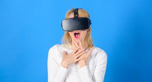 Woman watching virtual reality vision. Woman using VR device. Woman wearing virtual reality goggles in blue background. Futuristic 3d stock photo