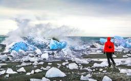 Woman watching waves crash against icebergs at Jokulsarlon glacial lagoon near Vatnajokull National Park, southeast Iceland.  royalty free stock photos
