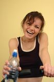 Woman with water. Woman laughing. Having a break from her fitness exercises Stock Images