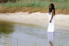 Woman In Water. Lonely African American woman stands downcast in shallow water with a sad pensive look on her face stock photography