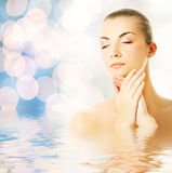 Woman in water. Beautiful young woman in water massaging her face Stock Image