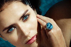 Woman at a water blue eyes  sapphire. A beautiful young woman with  stunning blue swimming naked in a pool, wearing a large sapphire ring on her index finger Royalty Free Stock Photography