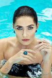 Woman at a water blue eyes sapphire. A beautiful young woman with stunning blue swimming in a pool, wearing a large sapphire ring on her index finger, nice Stock Photo