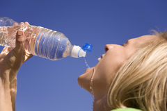 Woman and water bottle. A woman getting a drink from her water bottle Royalty Free Stock Photography