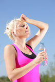 Woman with water bottle feels the heat of summer Royalty Free Stock Photography