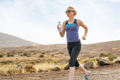 Woman with Water Bottle Fitness Run on Dirt Road. Woman with bottle of water on a fitness run on dirt road Royalty Free Stock Photography