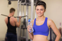 Woman with water bottle while man using lat machine in gym Royalty Free Stock Images