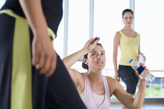 Woman with water bottle in studio in gym, wiping forehead Royalty Free Stock Photo