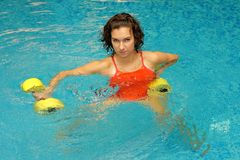 Woman in water with dumbbels Royalty Free Stock Images