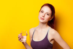 Woman with water glass after. Weight loss on yellow background Royalty Free Stock Images