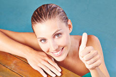 Woman in water holding thumbs up Stock Photo