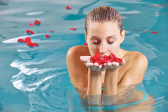 Woman in water with petals of roses Stock Photos