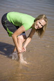 Woman in water playing. A woman playing and washing off her leg in the water Stock Image