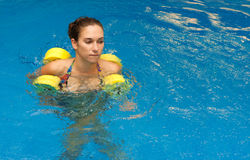 Woman in water stay with dumbbells Stock Image