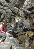 Woman and waterfall. Side view of young woman looking at rocky waterfall in countryside Stock Image