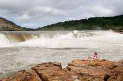 Woman, waterfall in background. Woman with wide waterfall at Arekuna, Venezuela in background, under cloudy sky with brown stones in foreground Stock Images