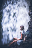 Woman on a waterfall deep in the tropical rain forest of Ubud, tropical Bali island, Indonesia. Exotic scene of tropics Royalty Free Stock Image