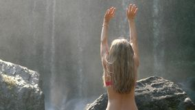 Woman By Waterfall. Rear view of young woman sitting in front of waterfall with her hands raised. Female tourist with her arms outstretched. Freedom, success stock footage