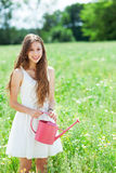 Woman with watering can Stock Images