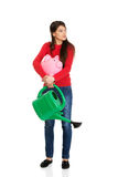 Woman with a watering can and piggybank. Royalty Free Stock Photos