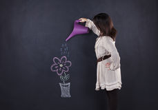 Woman watering a drawing plant Stock Image