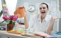 Woman watering flowers on desk Stock Photo
