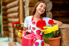 Woman watering flowers near the wooden cottage Stock Image