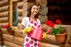 Woman watering flowers near the wooden cottage Stock Images