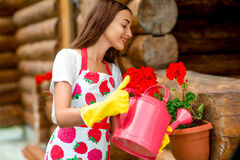 Woman watering flowers near the wooden cottage Royalty Free Stock Images