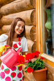 Woman watering flowers near the wooden cottage Royalty Free Stock Photography